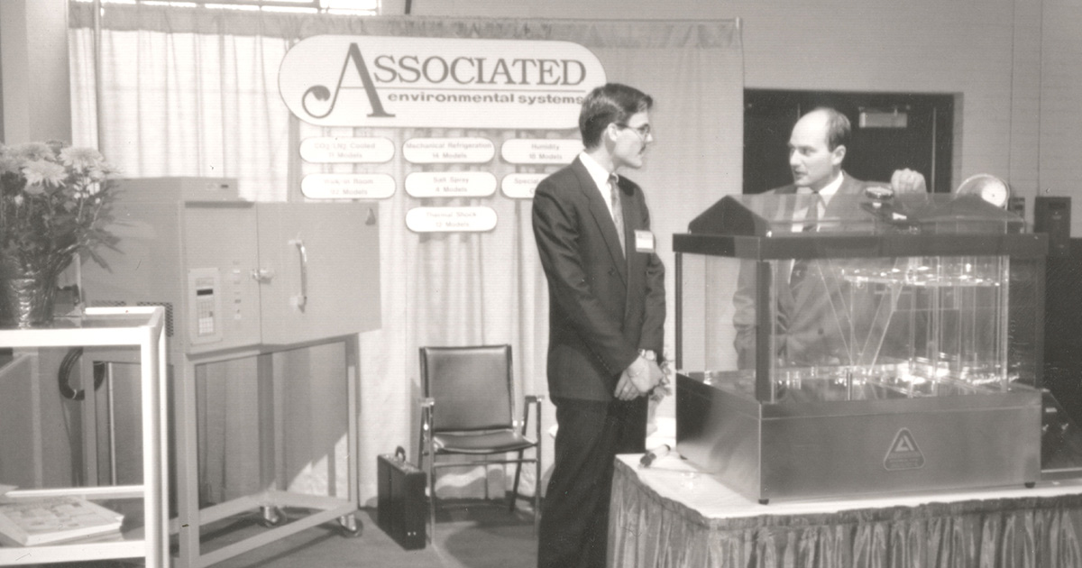 historic photograph of John O'Rourke standing next to AES' MX series salt spray test chamber