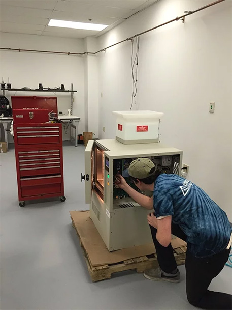 Service Tech working on test chamber by associated environmental systems