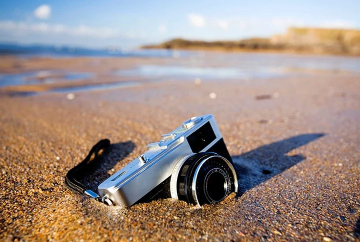Camera buried partially in sand