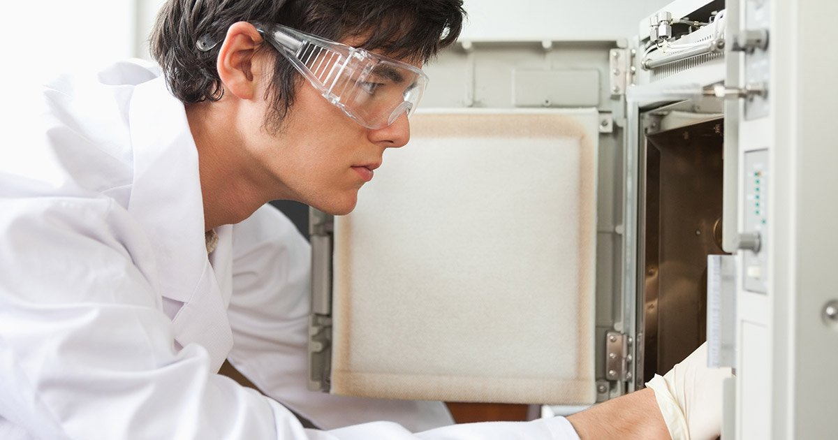 scientist reaching into an open benchtop test chamber